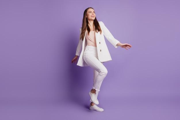 Крупным планом портрет мечтательной танцовщицы, выглядящей пустым пространством, носить формальный костюм, позирует на фиолетовой стене