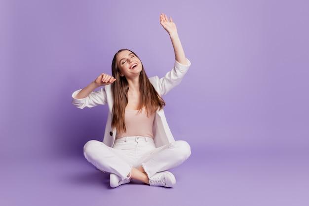 Крупным планом портрет мечтательной радостной дамы сидит на полу, смотрит пустое пространство, поднимает руки, позирует на фиолетовой стене