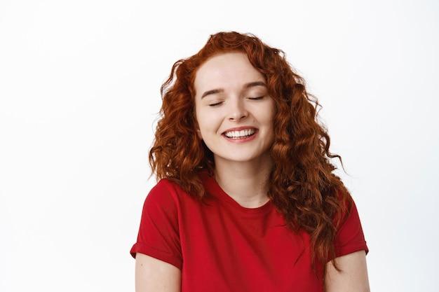 Крупным планом портрет мечтательной рыжей девушки-подростка закрывает глаза и улыбается, чувствуя счастье и радость, мечтая о чем-то, стоя у белой стены