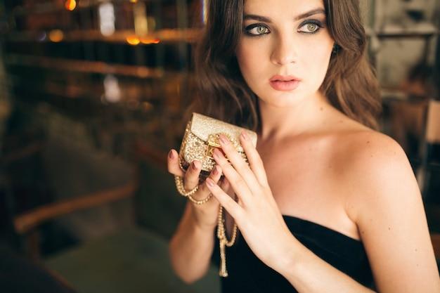 검은 벨벳 드레스, 이브닝 가운, 풍부한 세련된 숙녀, 우아한 패션 트렌드, 손에 황금 지갑을 들고 빈티지 카페에 앉아 우아한 아름다운 여자의 초상화를 닫습니다
