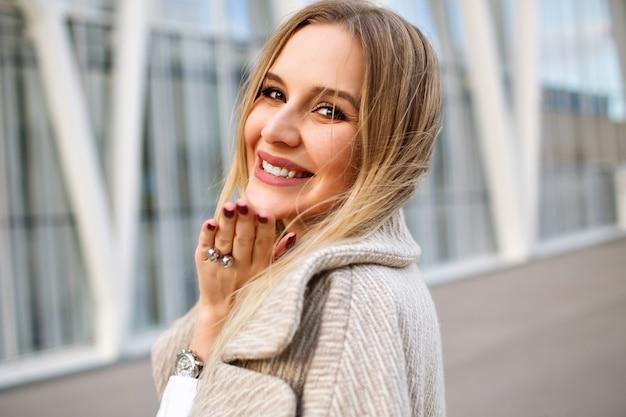 通りを身に着けているエレガントな金髪女性の肖像画を間近で身に着けているコート、自然なメイクアップ、官能的な顔と長いブロンドの髪、風の強い秋の天気。