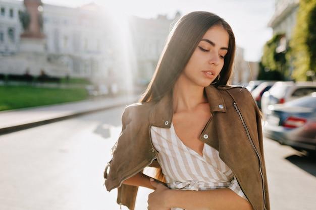 도시 배경에 카메라에 포즈를 취하는 갈색 재킷에 우아한 갈색 머리 소녀의 클로즈 업 초상화