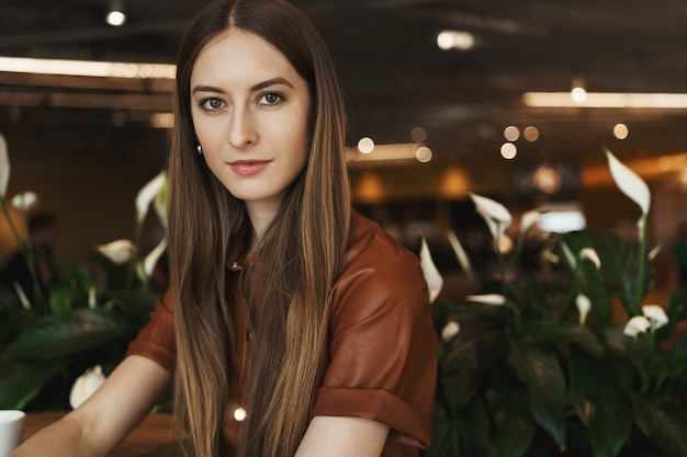 カフェのコーヒーテーブルに寄りかかってエレガントな魅力的な若い女性のクローズアップの肖像画。