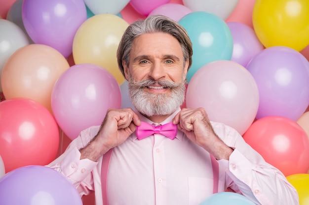 Макро портрет элегантного импозантного человека над красочными воздушными шарами