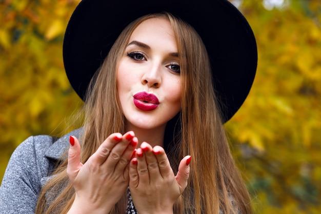 都市公園で秋の寒い日にポーズをとって、エレガントな黒い帽子、長い髪、明るいメイクを身に着けているエレガントなきれいなブロンドの女性の肖像画を閉じます。エアキスを送る