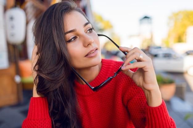 Крупным планом портрет элегантной романтической женщины с брюнетка волнистые волосы с стильные ретро очки и жених вязаный свитер. девушки отдыхают в современном кафе по утрам и пьют кофе.
