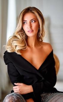エレガントな女性のクローズアップの肖像画。巻き毛の美しい髪の金髪の女性。美容メイクと健康な肌の女性のファッションの肖像画を持つ美しいブロンドの長い巻き毛の女性。