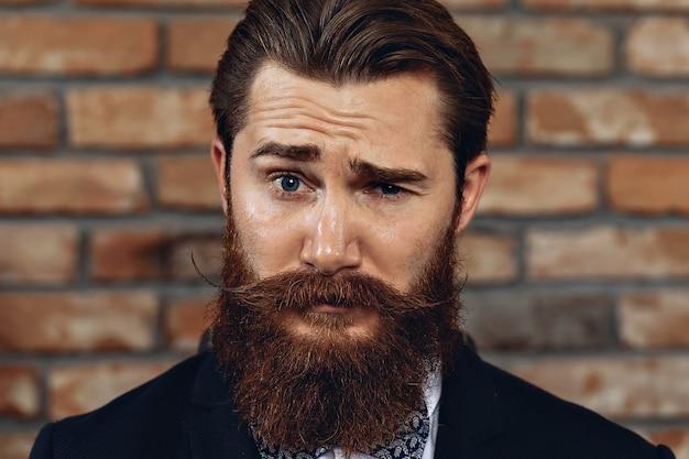 レンガの壁の背景にポーズをとってハッサーの口ひげとひげを持つ感情的な魅力的な男の肖像画を閉じます。コンセプト感情