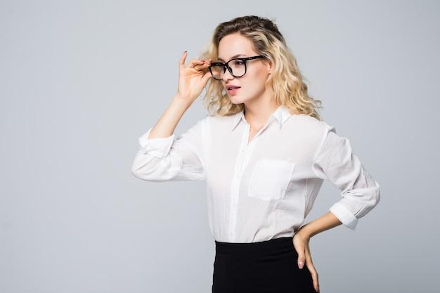 灰色の壁に分離された眼鏡をかけている感情的な若い女性の肖像画を閉じます。