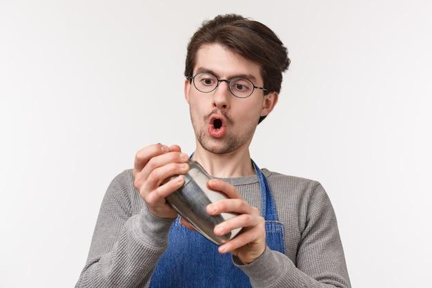 熱狂的な献身的な若い男性従業員のクローズアップの肖像画、バーテンダーは飲み物を作るのが好き、情熱を持ってシェーカーでカクテルを振る、興奮した白い壁に立っています