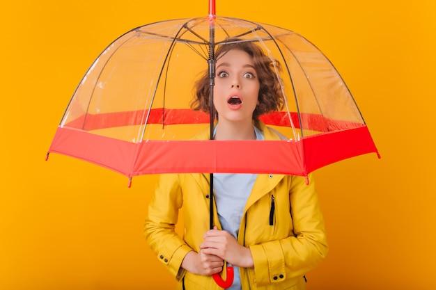 파라솔 아래 서 곱슬 헤어 스타일으로 열정적 인 여자의 클로즈업 초상화. 우산을 들고 비옷에 화가 여성 모델의 실내 사진.