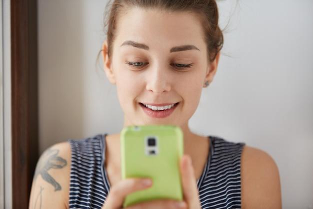 緑のスマートフォンでゲームをプレイするヨーロッパの女の子のクローズアップの肖像画。微笑んでディスプレイを見て、両手でガジェットを保持している若くて魅力的な女性。室内での昼光ショット。