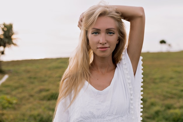 녹색 식물 해변의 배경에 카메라에 포즈 흰 옷을 입고 긴 머리를 가진 유럽 여자의 초상화를 닫습니다