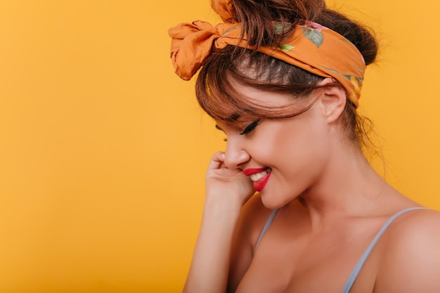Крупным планом портрет европейской женщины с загорелой кожей, позирующей с застенчивой улыбкой