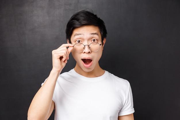 興奮して不思議に思った、興味をそそられるアジア人男性のタッチグラスのクローズアップの肖像画、興奮してカメラに興味を持って見て、口を開けて魅了されて、興味深い提案を聞いて、