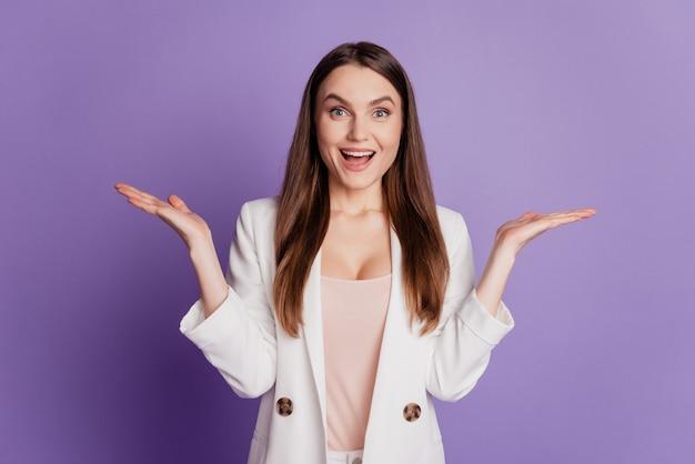 興奮したかわいい女性の肖像画をクローズアップ手を上げて口を開ける紫色の壁にポーズをとってフォーマルなスーツを着る