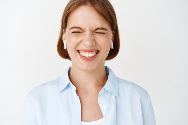目を閉じて笑って、ワイヤレスイヤホンで音楽を聴いて楽しんで、白い壁に立って興奮している女の子のクローズアップの肖像画