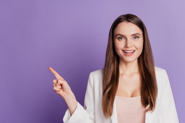 Крупным планом портрет возбужденной промоутер леди прямой палец пустое пространство носить формальный костюм позирует на фиолетовой стене