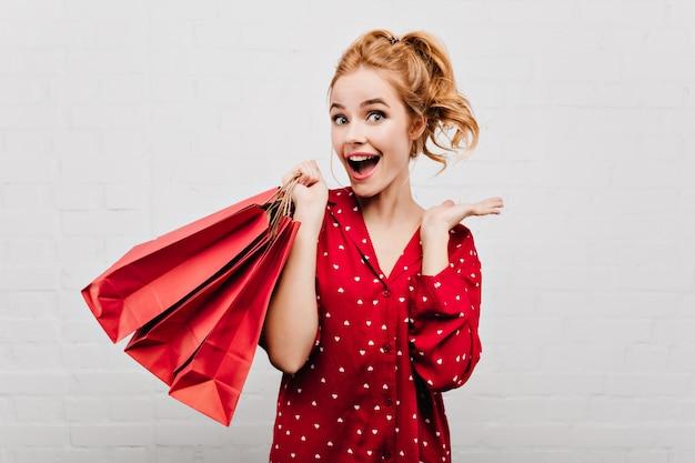 빨간 종이 봉지를 들고 물결 모양 헤어 스타일으로 흥분된 여자의 클로즈업 초상화. 흰 벽에 재미 잠옷에 감정적 인 여자
