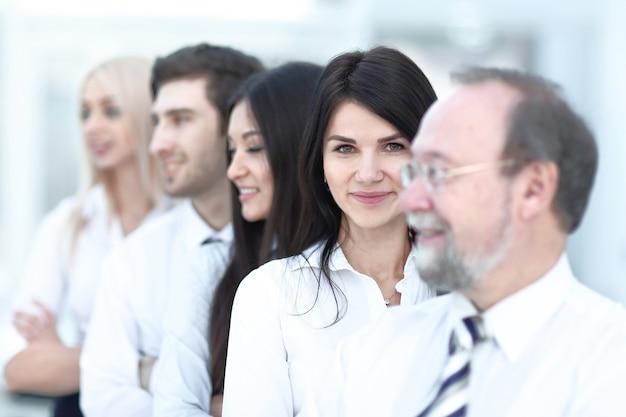 Макро портрет исполнительных деловых людей, стоящих в ряду в офисе и смотрящих в камеру. деловые люди.