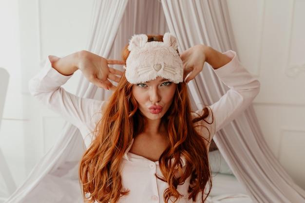 수면 마스크와 긴 물결 모양의 빨간 머리를 가진 종료 재미 있은 여자의 초상화를 닫습니다 침대에서 얼굴을 만든다