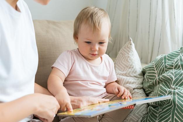 Крупным планом портрет безликой женщины, читающей книгу с серьезным ребенком на диване при естественном свете