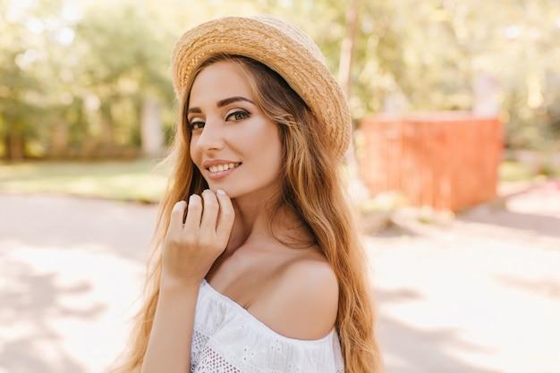 公園に立って晴れた日にふざけてポーズをとって魅力的な若い女性のクローズアップの肖像画。美しい薄緑色の目が笑顔で、あごに触れているゴージャスな女の子の屋外写真。