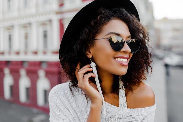 屋外ポーズスタイリッシュなアフロの毛でファッショナブルな黒人女性の肖像画を閉じます。都市の背景。黒いサングラス、帽子、白いイヤリングを着ています。トレンディなアクセサリー。満面の笑み。