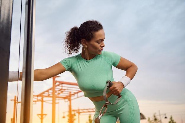 屋外の日の出でケーブルクロスオーバー機器を使用して、クロスオーバージムマシンで運動し、背中、肩、上腕三頭筋を曲げる女性アスリートのクローズアップポートレート。フィットネスとボディービルのコンセプト