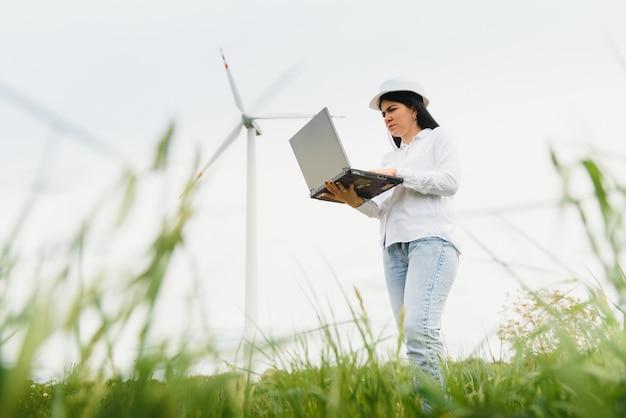 Крупным планом портрет женщины-инженера в шлеме, стоящего и использующего портативный компьютер, проверяя работу турбины ветряной мельницы на станции возобновляемых источников энергии.