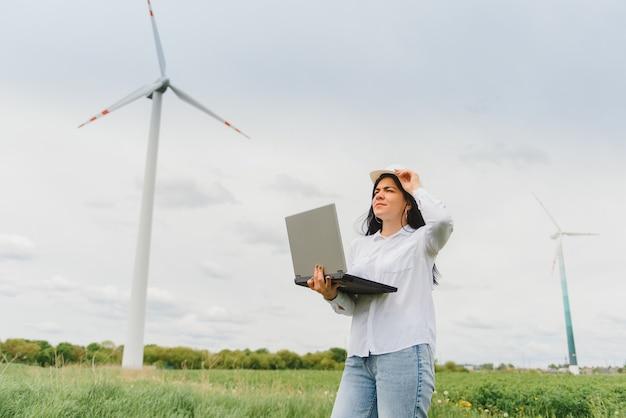 Крупным планом портрет женщины-инженера в шлеме, стоящего и использующего портативный компьютер, проверяя работу турбины ветряной мельницы на станции возобновляемых источников энергии. Premium Фотографии