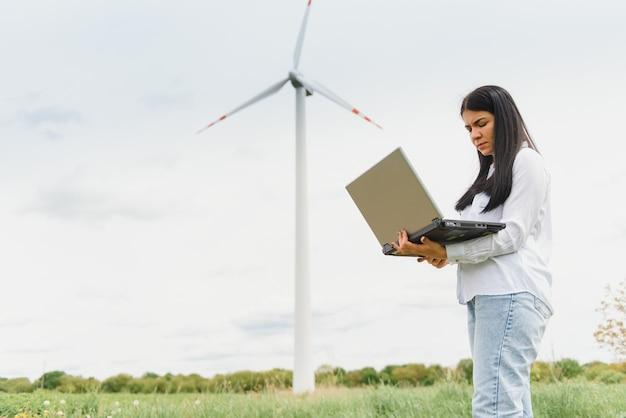 Крупным планом портрет женщины-инженера, стоящего и использующего портативный компьютер, проверяя работу турбины ветряной мельницы на станции возобновляемых источников энергии.