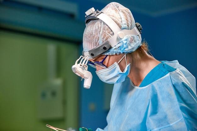 Крупным планом портрет женщины-врача-хирурга в защитной маске и шляпе во время операции.
