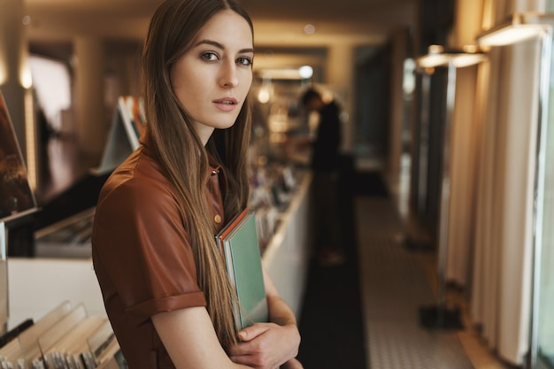 빈티지 상점이나 서점에서 쇼핑, 책을 들고 가슴을 눌렀다가 옆으로 보이는 여성 아가씨의 클로즈업 초상화.