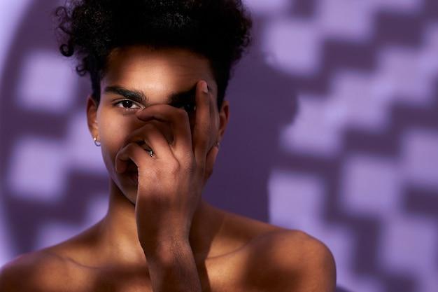 보라색 배경 트랜스젠더 젊은 남자에 그림자에서 포즈를 취하는 맞는 남성 모델의 초상화를 닫습니다