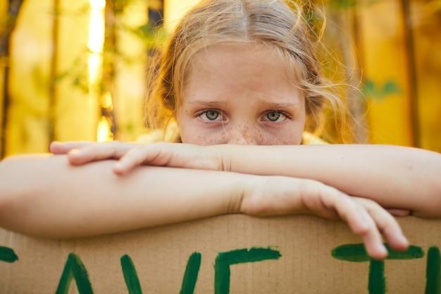 야외에서 행성 기호 저장을 통해 큰 파란 눈을 가진 카메라를보고 주근깨가 십 대 소녀의 초상화를 닫습니다