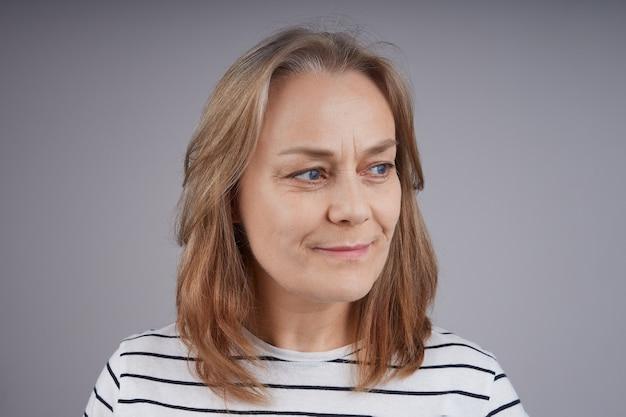 笑顔の縞模様のシャツでフレンドリーな年配の女性の肖像画をクローズアップ