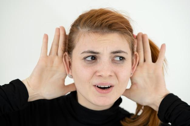 Закройте вверх по портрету смешной девушки держа ее уши руками как обезьяна.