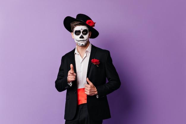 카메라에 손가락을 보여주는 뼈대 마스크와 재미있는 남자의 클로즈업 초상화. 무료 사진