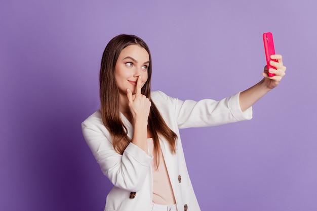 面白い女性の肖像画をクローズアップ携帯電話を保持し、紫の壁にポーズをとって自分撮りにフォーマルなスーツを着させる