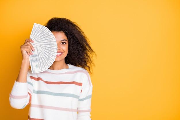 Крупным планом портрет девушки, скрывающей половину лица за деньги большого вентилятора