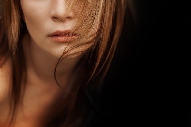 블랙에 긴 머리를 가진 여자 입술의 클로즈업 초상화. 공간 복사