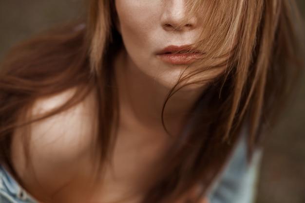 긴 머리를 가진 여자 입술의 클로즈업 초상화