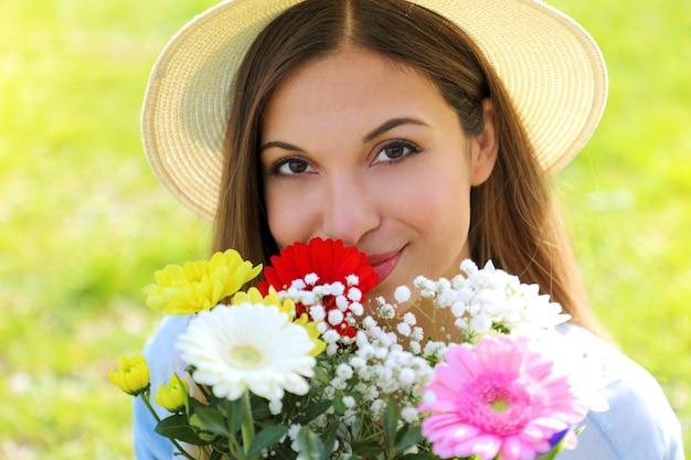 봄 시간에 카메라를보고 꽃의 꽃다발 냄새 모자와 여자의 초상화를 닫습니다