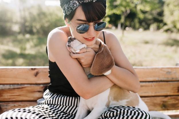 부드럽게 미소로 그녀의 비글 강아지를 껴 안은 기쁜 갈색 머리 아가씨의 클로즈업 초상화.