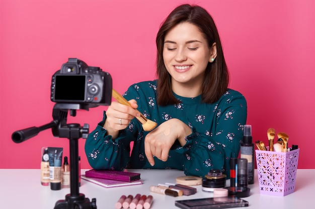 スタイリッシュなブラウスを着て、メイクアップブラシを持って、彼女の手にファンデーションを塗りつけ、メイクの特別なテクニックを見せて、見栄えのよい細身のポジティブモデルの肖像画を閉じます。美容コンセプト。