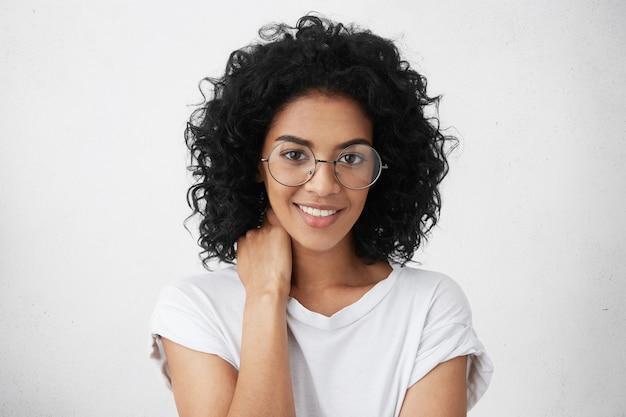 어두운 피부와 검은 털복숭이 머리카락을 가진 잘 생긴 학생 소녀의 초상화를 닫습니다