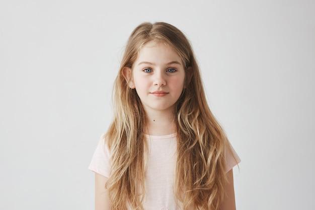 学校での写真撮影にポーズをとって、穏やかな表情で、ピンクのドレスを着た金髪の見栄えの良い若い女の子の肖像画を間近します。