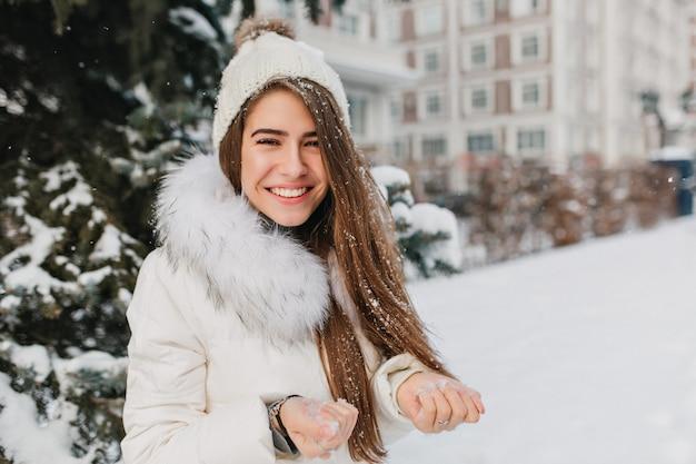 눈을 손에 들고 웃 고 화려한 금발 여자의 클로즈업 초상화. 마당에서 겨울 아침을 즐기고 누군가와 놀고 화려한 여자.
