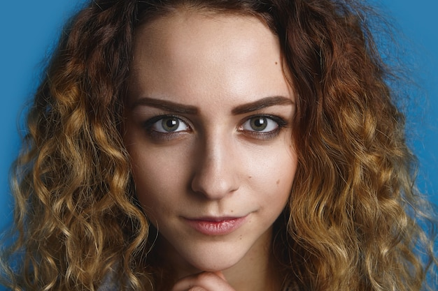 美しい鋭い緑色の目と不思議な笑顔で見つめているボリュームのある髪を持つゴージャスな魅力的な若い女性の肖像画をクローズアップ。美容、スキンケア、スタイル、ファッションのコンセプト